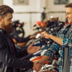 Man handing motorcycle keys to another man