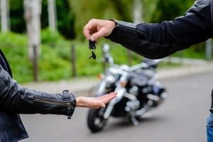 Motorcycle Rider Giving Keys to Another Rider