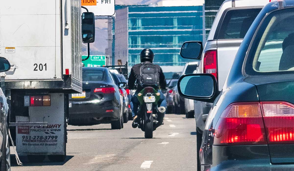 motorcycle riding between cars on road