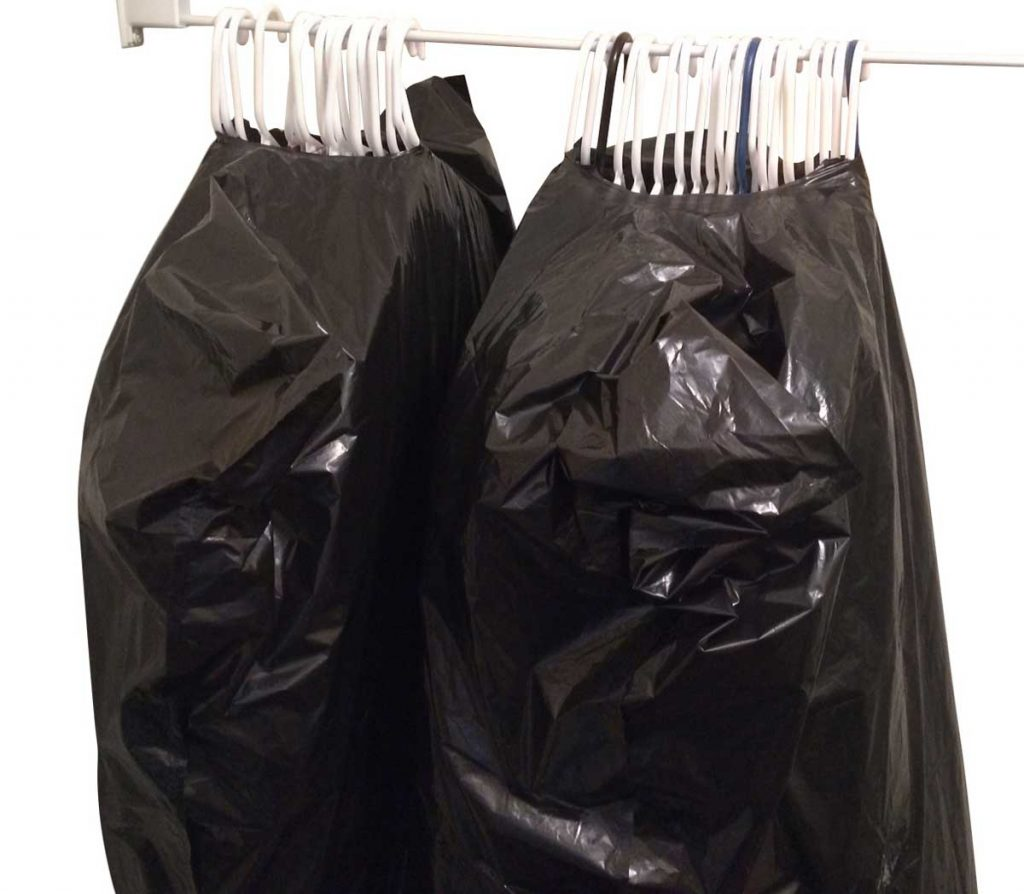 Clothes on hangars wrapped in trash bags