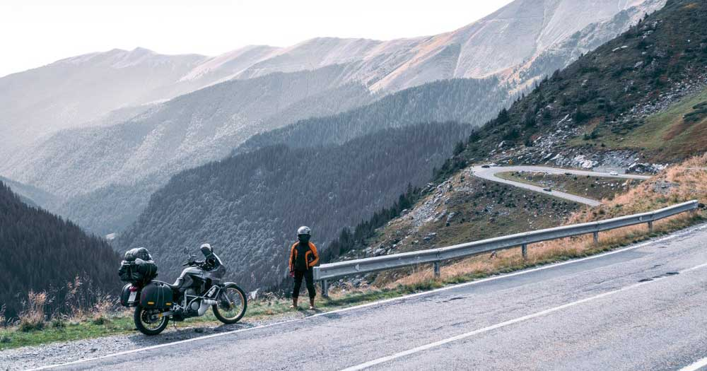 Motorcycle rider sanding in from of her bike on the transfagarasm highway